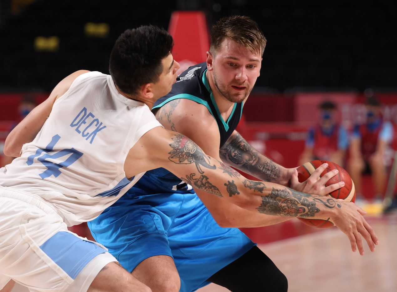 Slovenia's Luka Doncic (77) is defended by Argentina's Gabriel Deck (14) during the postponed 2020 Tokyo Olympics at Saitama Super Arena on Monday, July 26, 2021, in Saitama, Japan. Slovenia defeated Argentina 118-100. (Vernon Bryant/The Dallas Morning News)