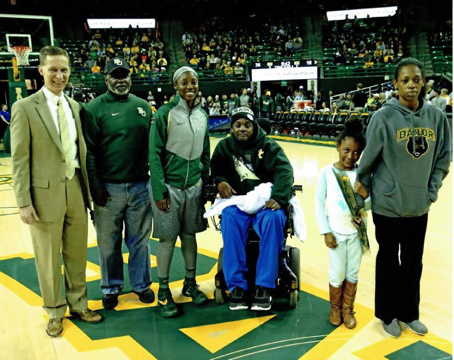 Alexis Jones with her family on the court at a Baylor basketball game