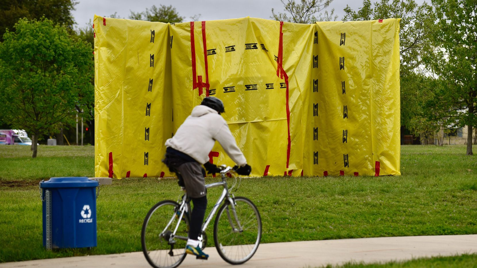 A man rode a bicycle in front of the now-covered monument honoring musicians Jimmie and Stevie Ray Vaughan at Kiest Park in Oak Cliff on Tuesday.
