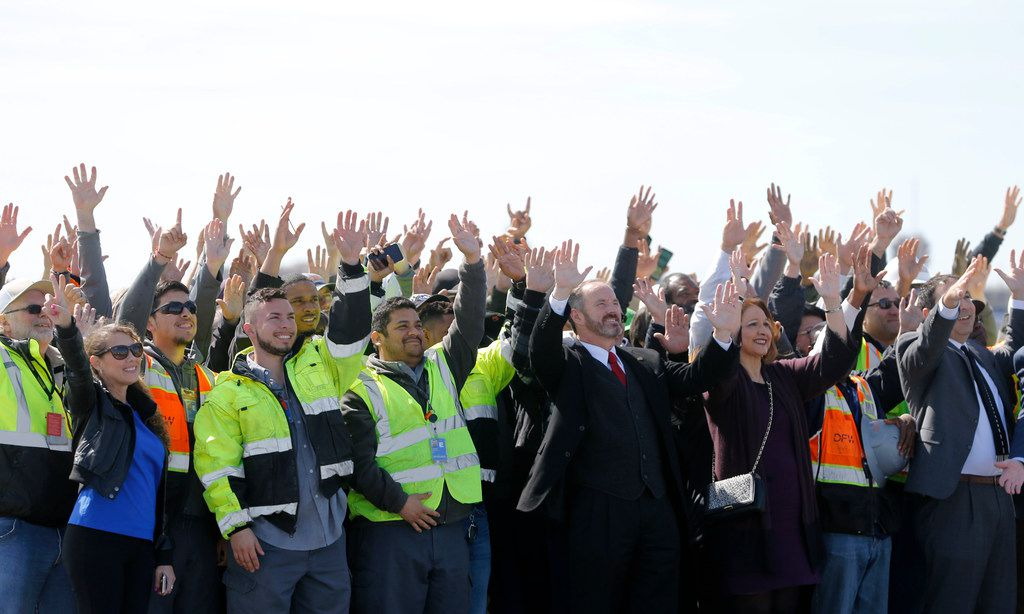 Employees wave for an employee photo taken on runway 17C at DFW International Airport on Monday, February  25, 2019. Runway 17C/35C was resurfaced with weather-resistant asphalt.