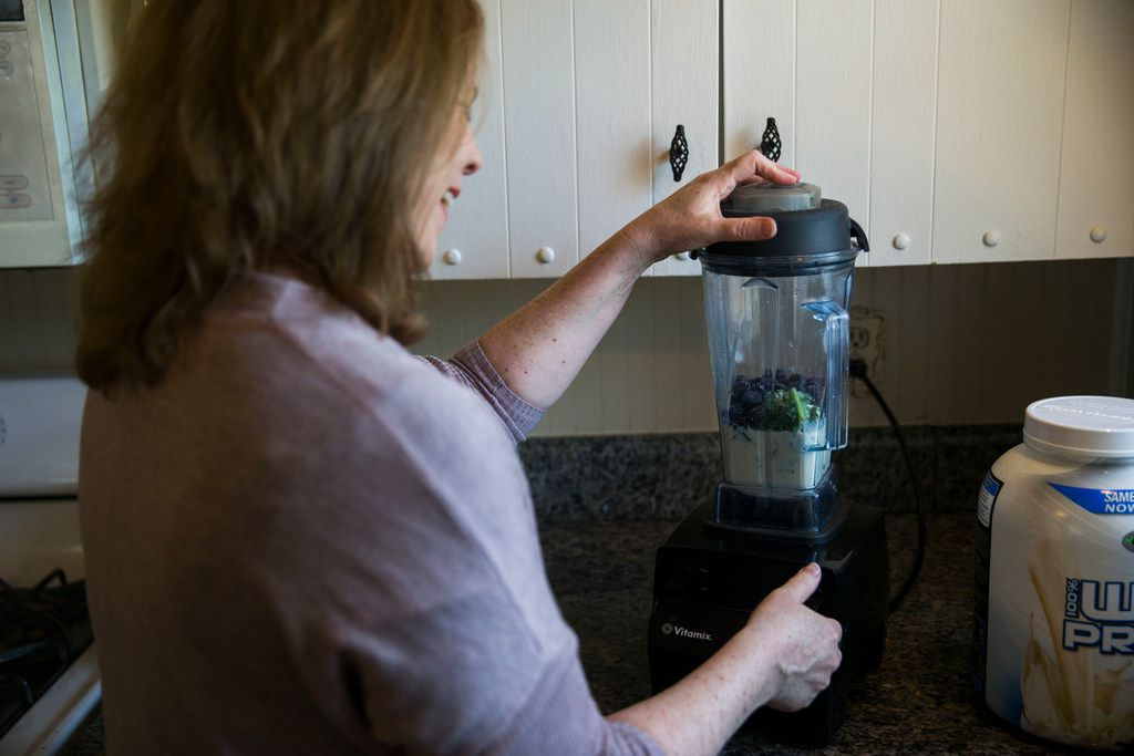 Author Kim Horner makes a smoothie with kale, blueberries, vanilla protein powder and soy milk at her home in Richardson.