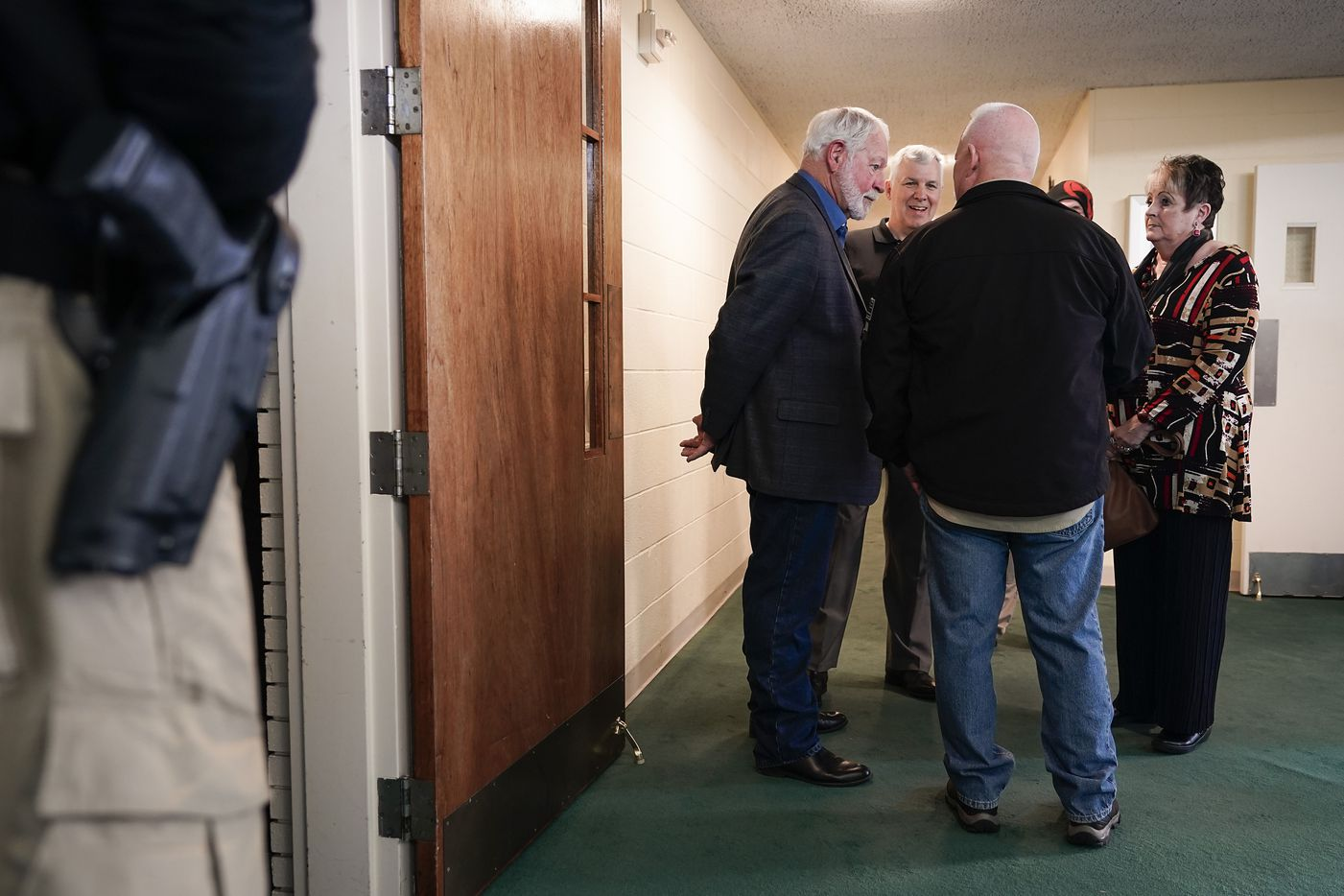 A member of the event security team stands at the doorway to the sanctuary at North Pointe Baptist Church as, from left, Jack Wilson, Mike Swihart, Greg Stevens and Cheryl Linam chat in the lobby during a  church safety seminar on Sunday, Jan. 26, 2020, in Hurst, Texas. Wilson, the head of the West Freeway Church of Christ volunteer security team who stopped a gunman at the church in White Settlement. Swihart, an off duty police officer at the time, stopped a deadly domestic dispute in the parking lot of his church in Fort Collins, Colo. in 1992. Stevens, then a Garland police officer, took down two terrorists at Curtis Culwell Center in 2015. Linam lost her 7-year old daughter in a shooting at First Baptist Church in Daingerfield, Texas in 1980.