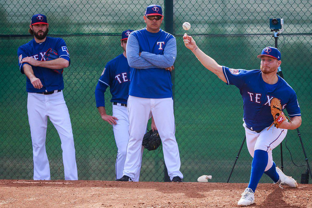 Texas Rangers pitcher Shelby Miller throws in the bullpen as pitching coach Julio Rangel (center) and pitcher Jason Hammel look on during a spring training workout at the team's training facility on Friday, Feb. 15, 2019, in Surprise, Ariz.. (Smiley N. Pool/The Dallas Morning News)