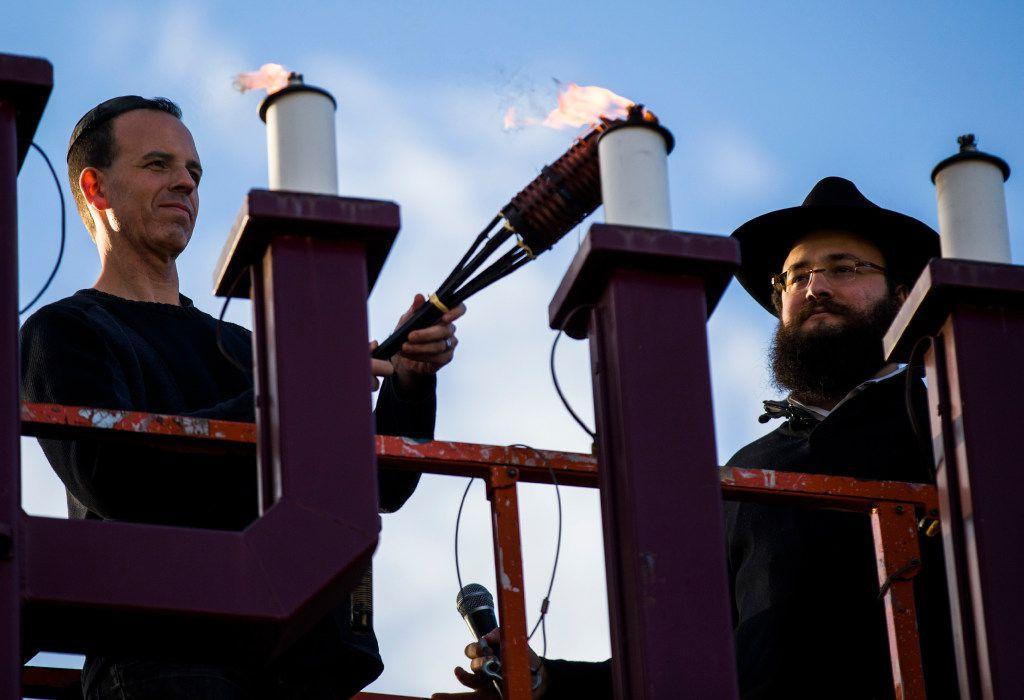 Evan Bundis, left, and Rabbi Moshe Naparstek, right, light large menorah at the Aaron Family Jewish Community Center of Dallas.