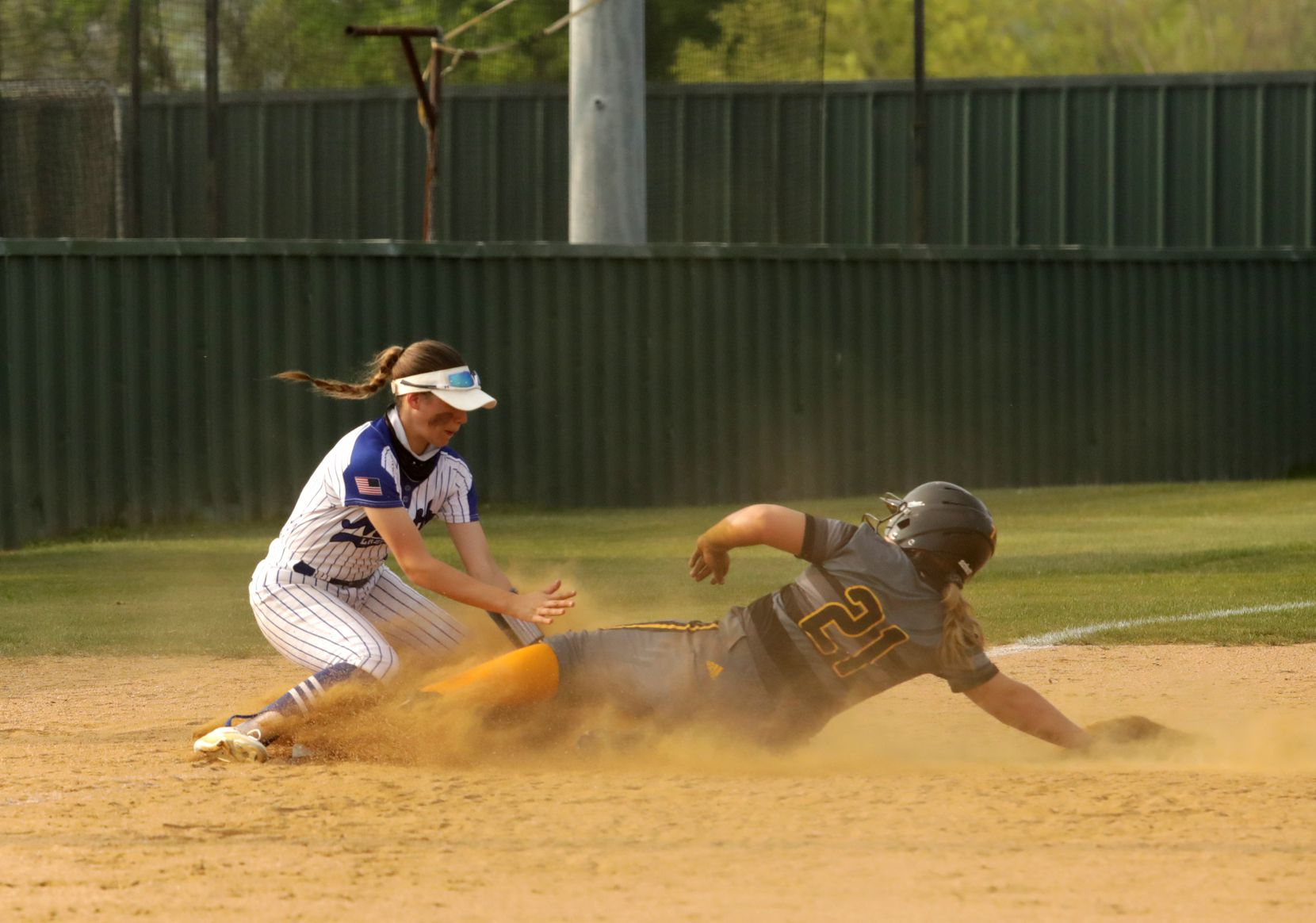 Hannah Reyes, left, guards third base and Katie Kretz slides in during a softball game between Forney at North Forney at North Forney High School in Forney, TX, on Apr. 9, 2021. (Jason Janik/Special Contributor)