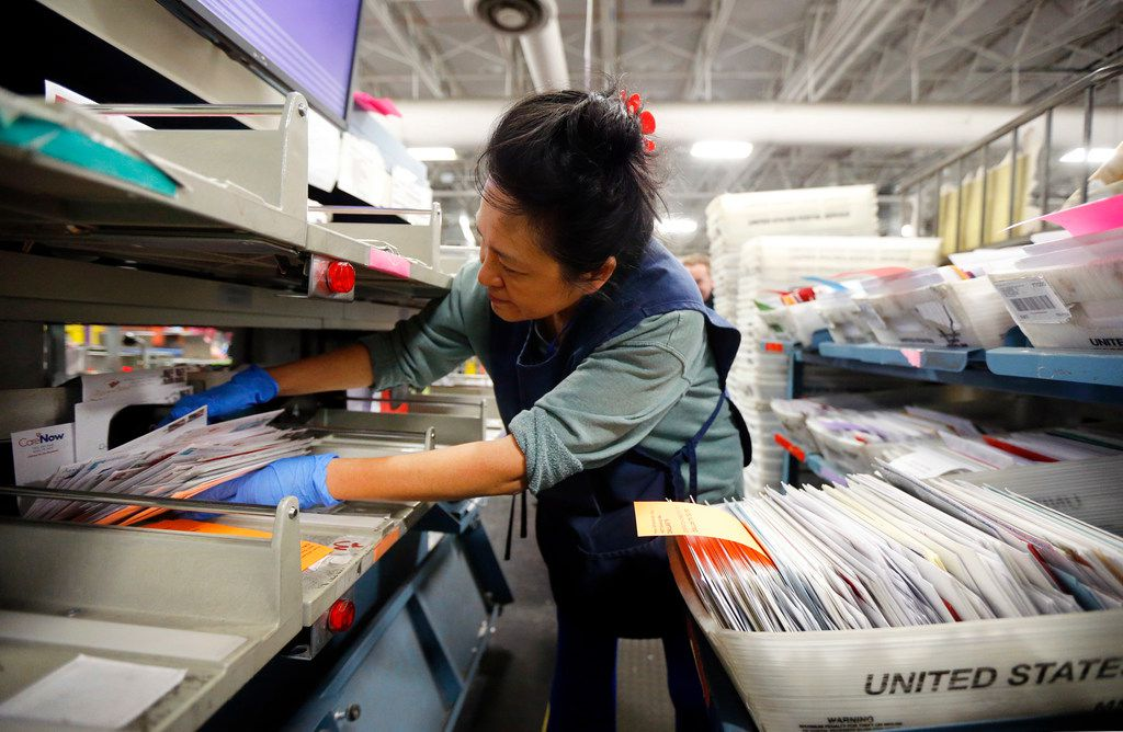Clerk Petty Chow grabs a handful of canceled mail after it had been sorted in the Advanced Facer Canceler System (AFCS, right) at the US Postal Service's North Texas Processing & Distribution Center in Coppell, Texas, Thursday, December 14, 2017.