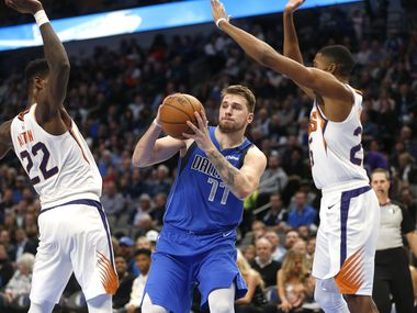 Dallas Mavericks guard Luka Doncic (77) looks to pass as Phoenix Suns center Deandre Ayton (22) and Phoenix Suns forward Mikal Bridges (25) defend during the second half of an NBA basketball game Tuesday, Jan. 28, 2020, in Dallas.