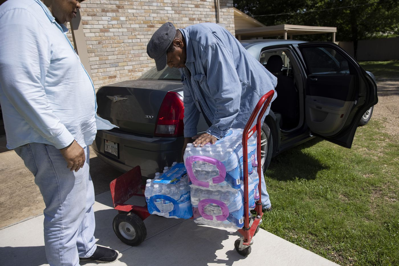 Jerone Roy (right) helps brother Deacon Bert Roy III load cases of water to distribute around the community at Mt. Zion Baptist Church on Wednesday, May 26, 2021, in Sandbranch. (Juan Figueroa/The Dallas Morning News)