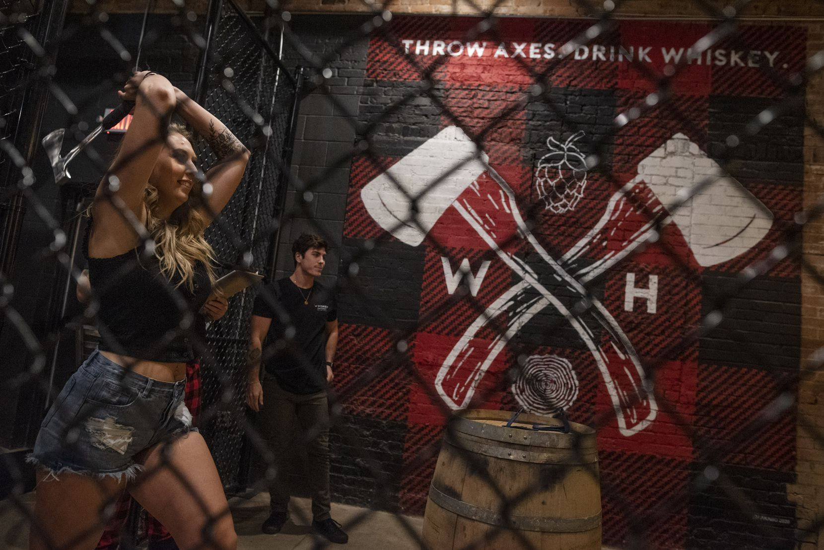 Customers at Whiskey Hatchet throw axes in designated bays. Here, staffer Paige Blaylock shows how to throw.