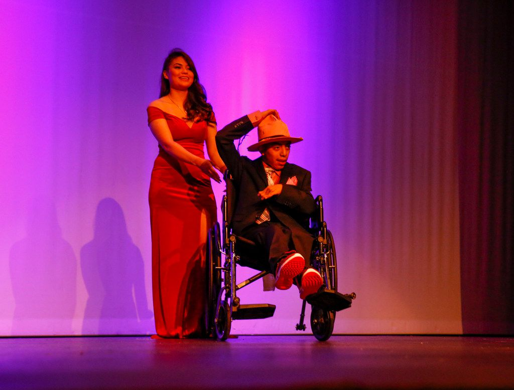 Jazmine Valdez Ruiz walks on stage with Aaron Osorio during a fashion show at Thomas Jefferson High School in Dallas on Wednesday, May 8, 2019. The Mark Cuban Heroes Basketball Center's Suit Up Experience provided custom-made suits from Lombardo Custom Apparel for 10 young men with special needs at Thomas Jefferson High School.