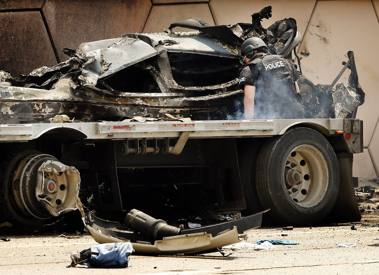 A SWAT team member looks inside the burned out vehicle that was trapped between the semi trailer and wall following a high speed chase on eastbound Interstate 30 at Cooper St. in Arlington  Friday, June 9, 2017. Police talked the man out of the truck. (Tom Fox/The Dallas Morning News)