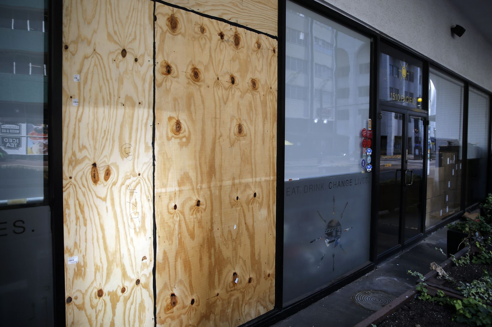 Plywood has been installed to cover the spot where one of Café Momentum's large street-side windows was broken out. Soon a manifesto, from the voices of interns and staff, will be placed on the plywood.
