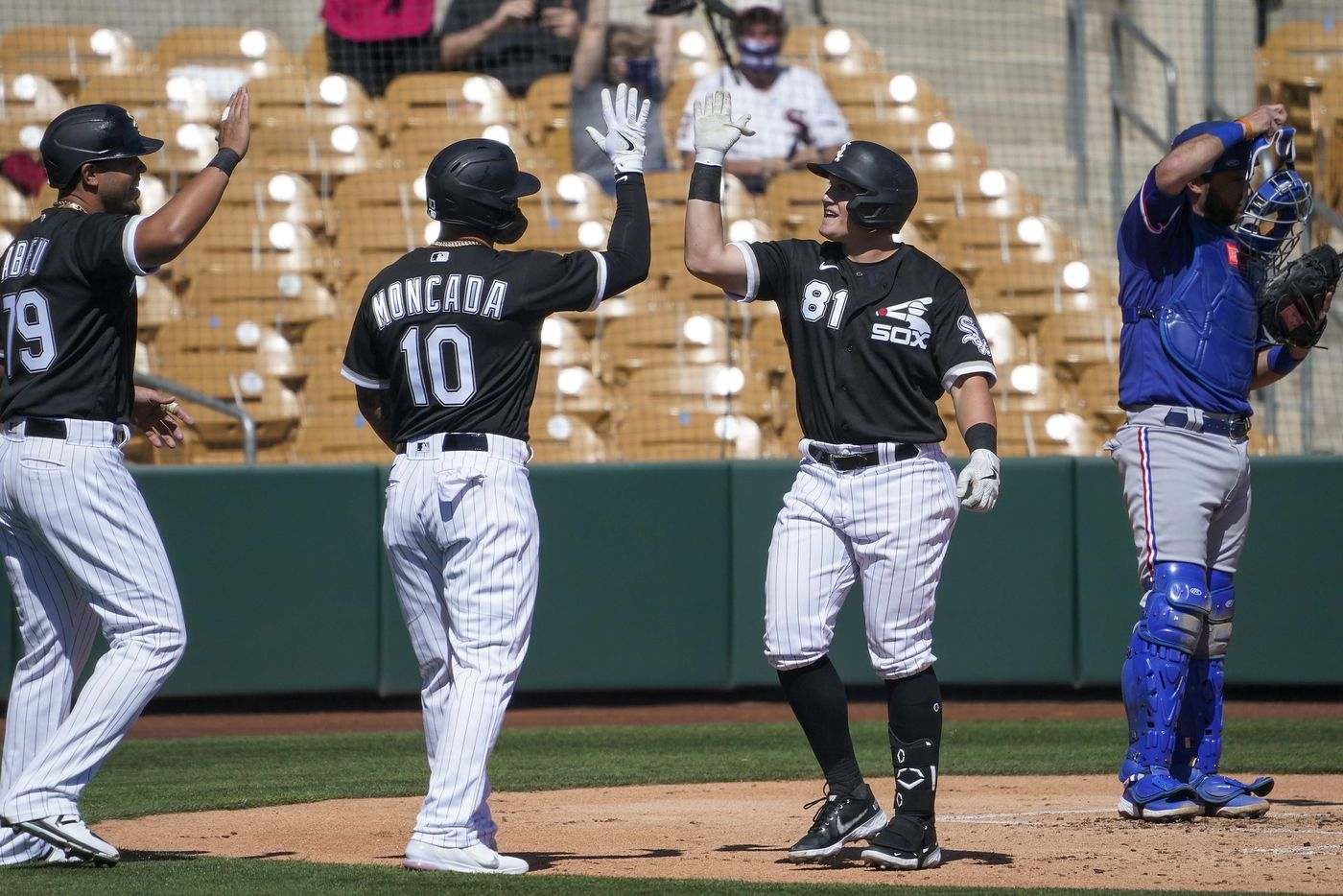 Chicago White Sox designated hitter Andrew Vaughn (81) celebrates with teammates Yoan Moncada and Jose Abreu after driving them in on a 3-run home run off of Texas Rangers pitcher Kohei Arihara during the first inning of a spring training game at Camelback Ranch on Tuesday, March 2, 2021, in Phoenix, Ariz.