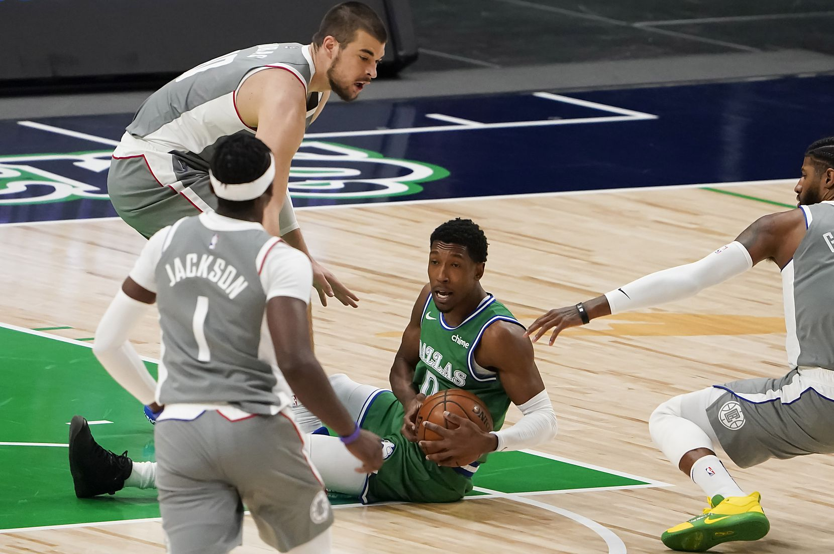 Dallas Mavericks guard Josh Richardson (0) grabs a loose ball between LA Clippers center Ivica Zubac (40), guard Paul George (13) and guard Reggie Jackson (1) during the first quarter of an NBA basketball game at American Airlines Center on Wednesday, March 17, 2021, in Dallas.