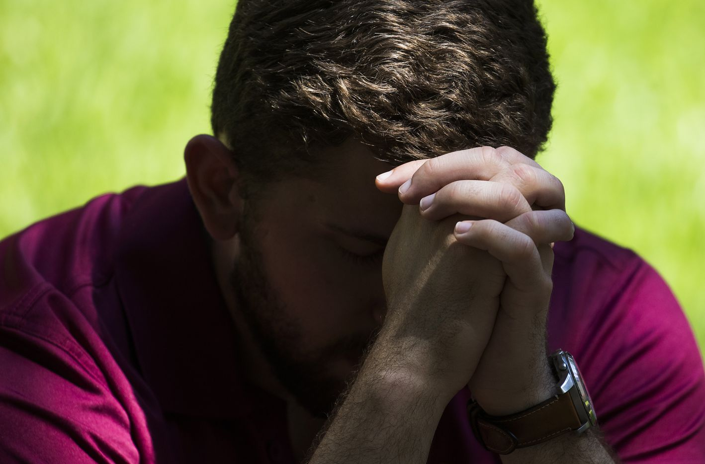 Dakota Loupe bows his head in prayer during a day of remembrance for last year's police ambush organized by Faith Forward Dallas at Thanks-Giving Square.