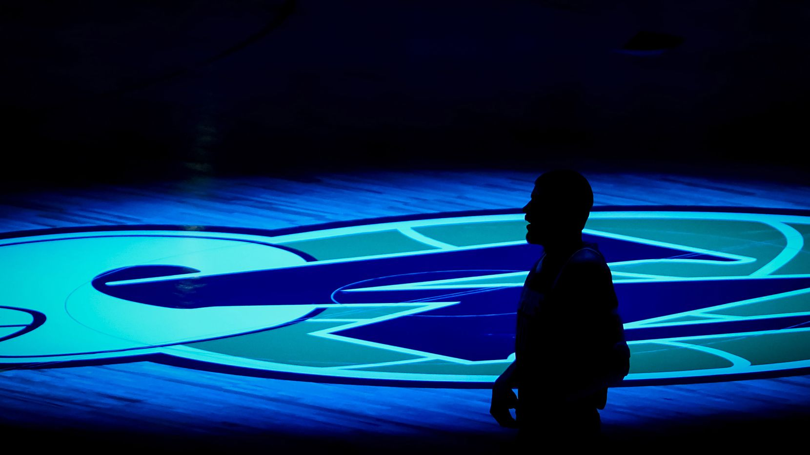 A player is silhouetted against the Dallas Mavericks logo before an NBA basketball game at American Airlines Center on Wednesday, March 17, 2021, in Dallas.