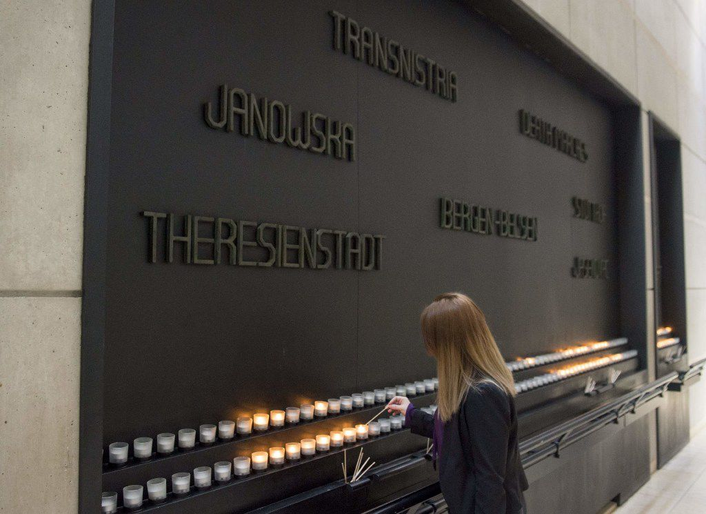 A woman lights a Memorial Candle during an International Holocaust Remembrance Day Commemoration at the United States Holocaust Memorial Museum in Washington, D.C., Jan. 27, 2017.
