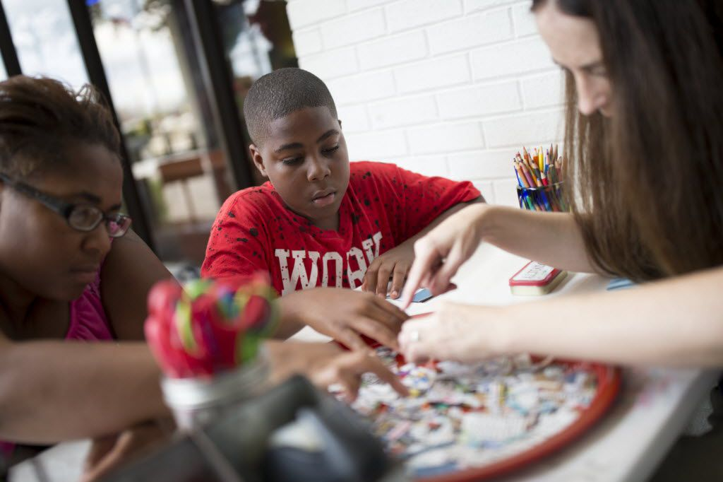 Kendrick Linnear (center), 11, of Dallas participates in a workshop led by artist Lisa Huffaker (right) and his mother, Brandy Redwine, making zines during Make Art with Purpose at Dallas West Branch Library earlier in August. (Ting Shen/The Dallas Morning News)