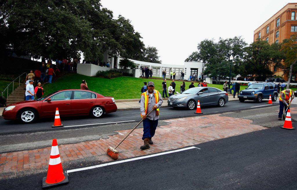 Dallas city workers repair the asphalt on Elm Street in Dealey Plaza as people visit Dealey Plaza on November 21, 2013.