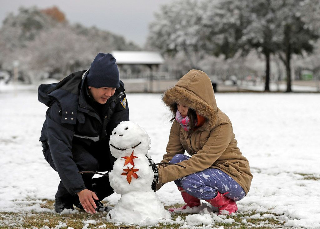 Houston Fire Department firefighter Phuoc Ngo, left, and his wife Christine Co build a snowman Friday, Dec. 8, 2017, in Spring, Texas, north of Houston. Rare snowfall in many parts of southern Texas has knocked out power to thousands, caused numerous accidents along slick roadways and closed schools. The weather band brought snow to San Antonio, Corpus Christi, Houston and elsewhere.