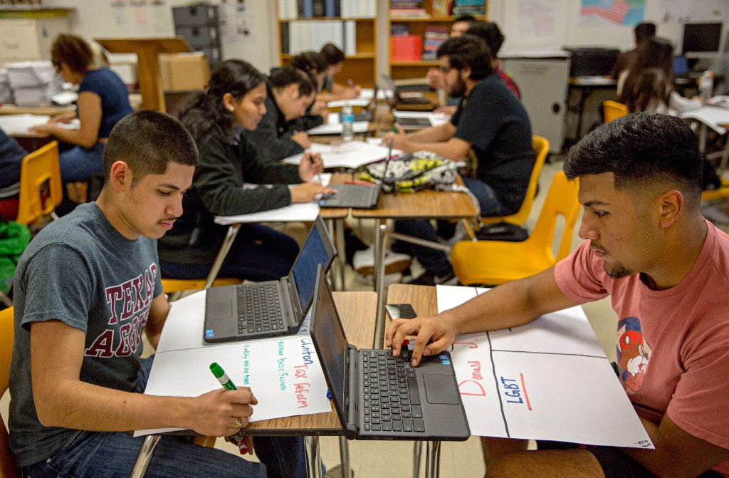 In this file photo, Andy Noyola (left) and Eric Diaz worked on posters listing presidential candidate platforms during a class at Irving High School. (G.J. McCarthy/The Dallas Morning News)