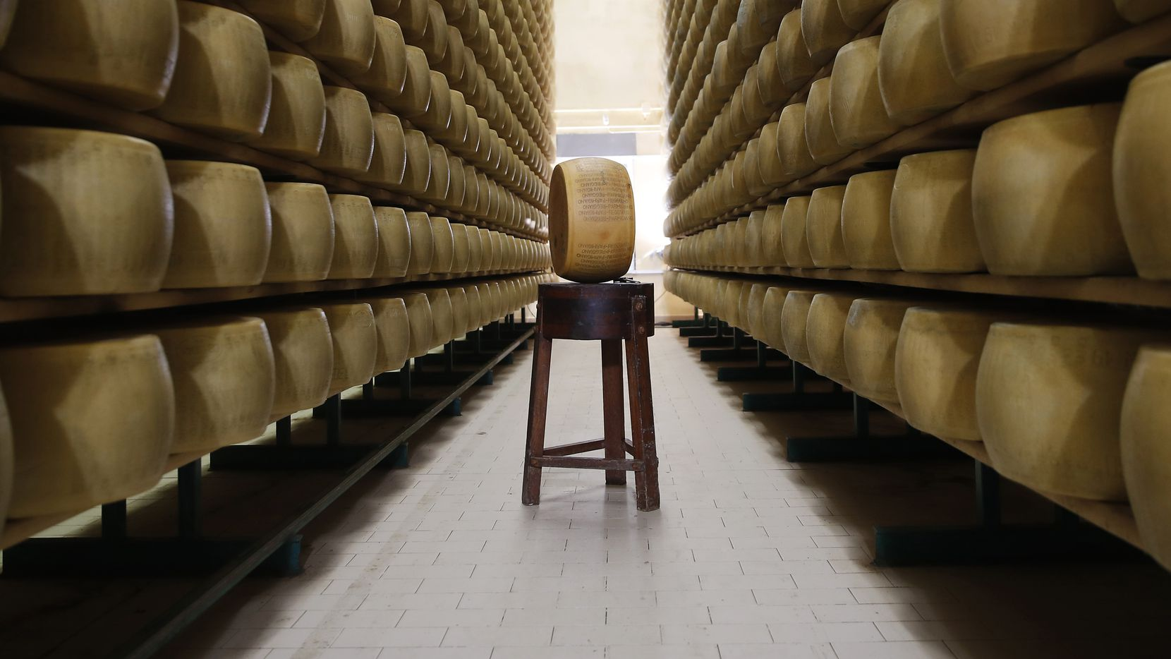 In this photo taken Tuesday, Oct. 8, 2019, Parmigiano Reggiano Parmesan cheese wheels are stored in Noceto, near Parma, Italy.