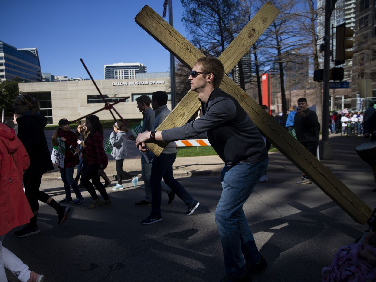 Jacob Niemeier carries a cross from the the Cathedral Santuario de la Virgen de Guadalupe to the Earle Cabell Federal Courthouse during the North Texas March for Life on Saturday, Jan. 18, 2020.