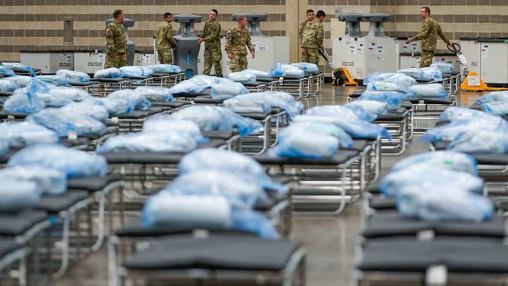 Members of the Texas Army National Guard unpack crates of supplies as they set up a field hospital in response to the new coronavirus pandemic at the Kay Bailey Hutchison Convention Center on Tuesday, March 31, 2020, in Dallas.