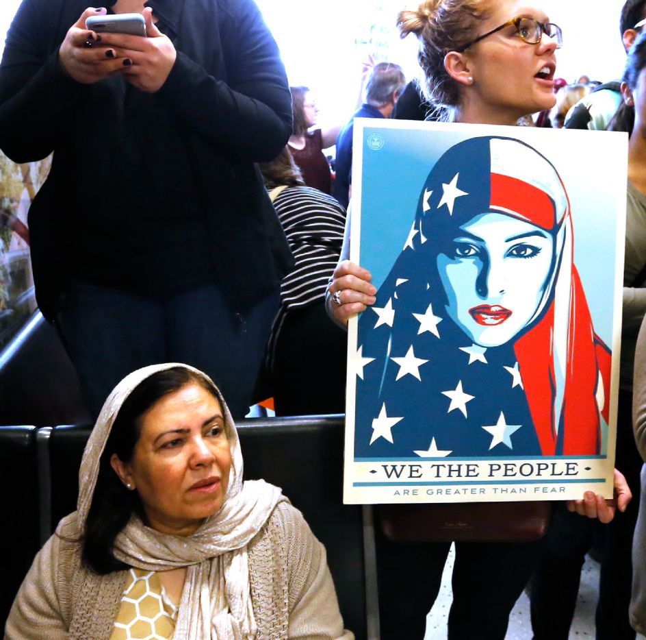 Protesters chant as they hold signs at the international arrivals gate in Terminal D at DFW Airport on Sunday, January 29, 2017. (Louis DeLuca/The Dallas Morning News)