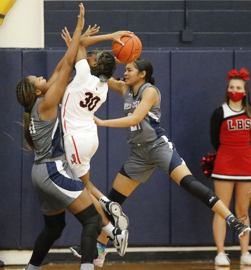Frisco Liberty High School guard Jazzy Owens-Barnett (30) drives in-between Wylie East High School forward Akasha Davis (41) and Wylie East High School forward Aleena Dawkins (21) during the first half as Frisco Liberty High School hosted Wylie East High School in the girls basketball Class 5A Region II final at McKinney High School on Tuesday, March 2, 2021.  (Stewart F. House/Special Contributor)