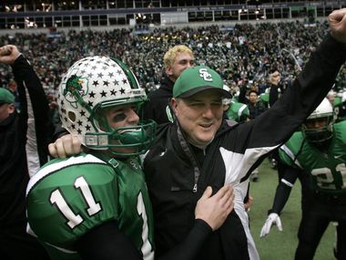 Southlake Carroll head coach Todd Dodge (right) and his sophmore son Riley Dodge (11) celebrate their 5A Division II Championship win over Katy at Texas Stadium , Saturday, December 16, 2005.
