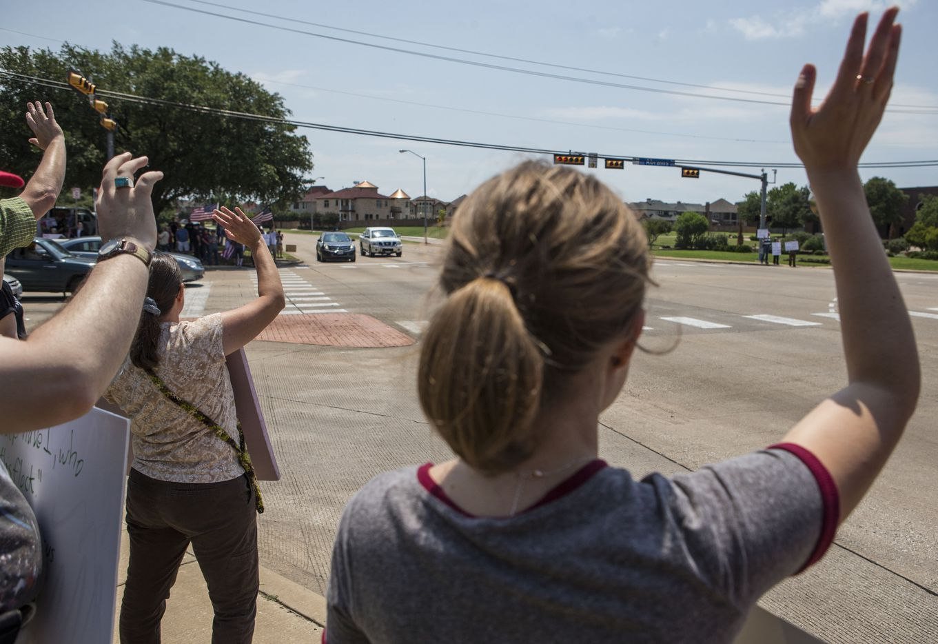Counter-protesters demonstrating against an anti-Shariah protest wave to passing cars Saturday, June 10, 2017, at the intersection of Abrams Road and Centennial Boulevard in Richardson, Texas. (Ryan Michalesko/The Dallas Morning News)