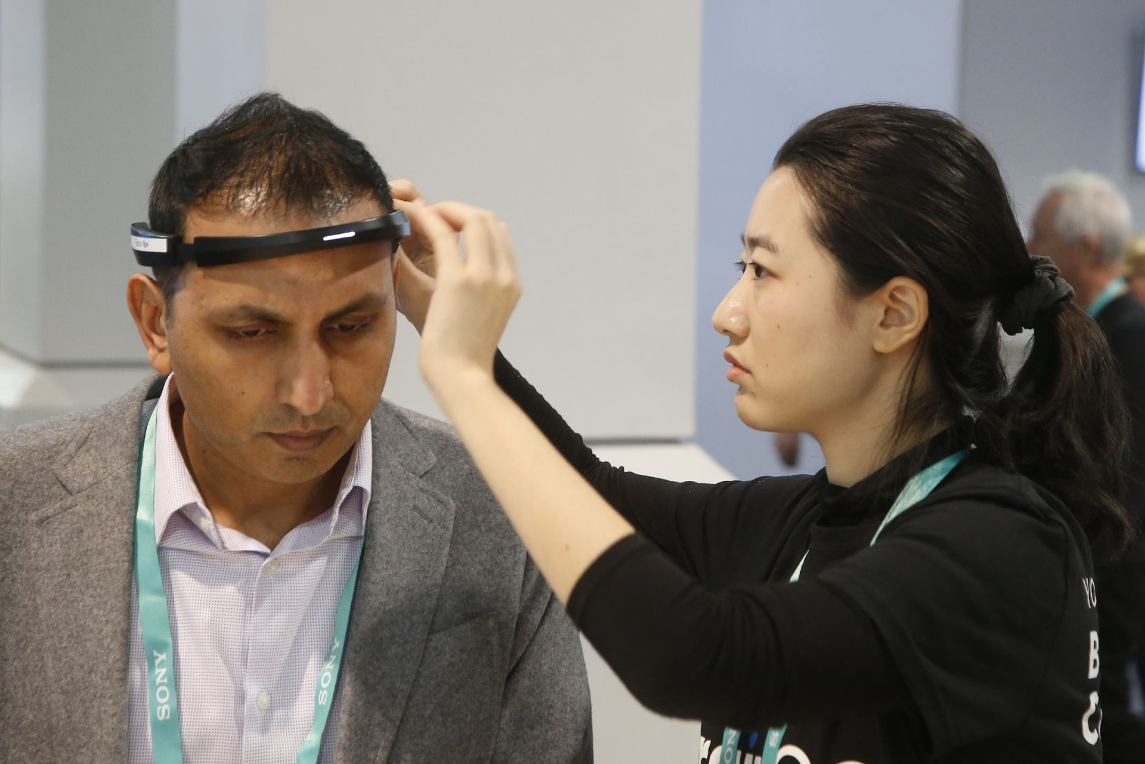 Yuwei Gu, right, of Ampligence, helps Ammad Khan with the BrainCo brainwave-sensing headband before linking with its software platforms. (AP Photo/Ross D. Franklin)