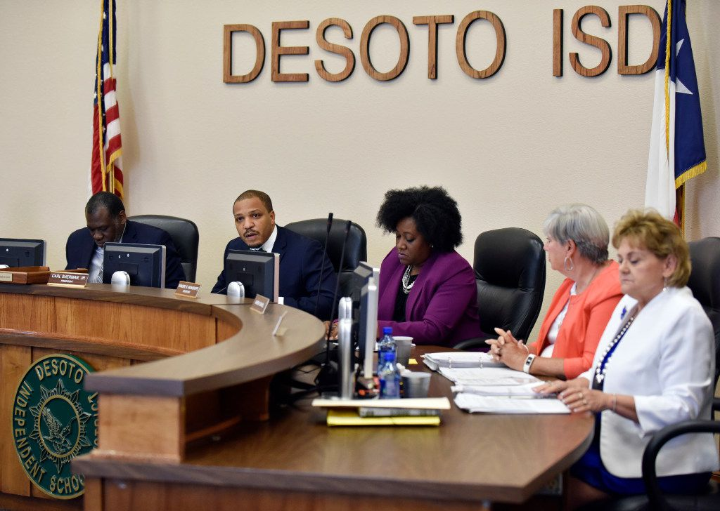 DeSoto school board president Carl Sherman Jr. (second from left) conducts a school board meeting to discuss  the contract of DeSoto football head coach Todd Peterman on Monday.  Superintendent David Harris sits at far left, while board members Sandre Moncriffe, Karen Daniel and Kathy Goad sit at right.