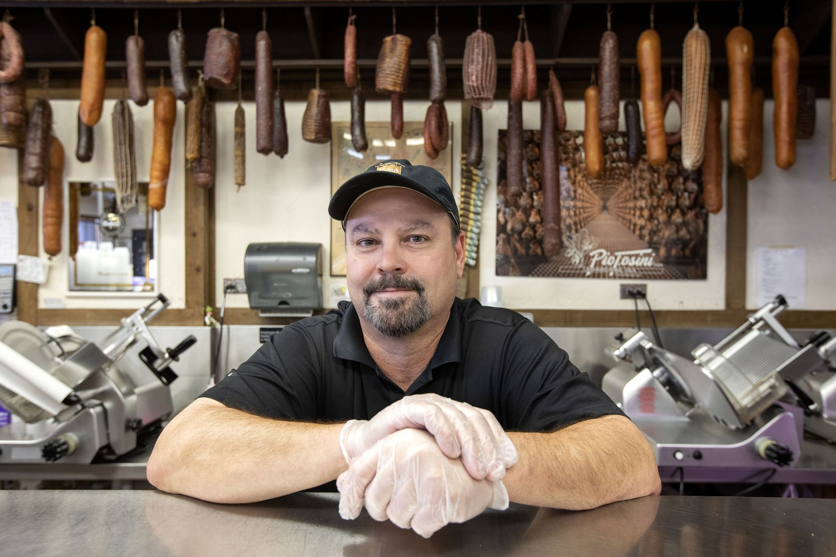 Karl Kuby Jr., owner of Kuby's Sausage House and European Market, poses for a portrait behind the counter.