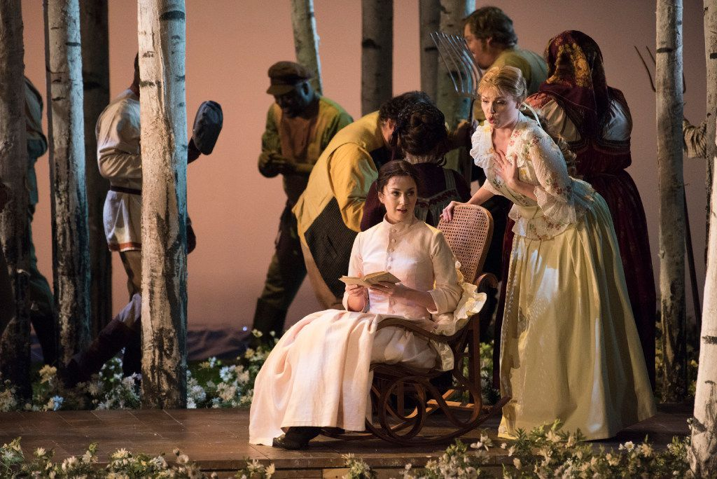 """The sisters Tatyana (Svetlana Aksenova, seated) and Olga (Kai Ruutel, bending over her) are contrasted in the Dallas Opera's dress rehearsal of """"Eugene Onegin"""" at the Winspear Opera House. (Rex C. Curry/Special Contributor)"""