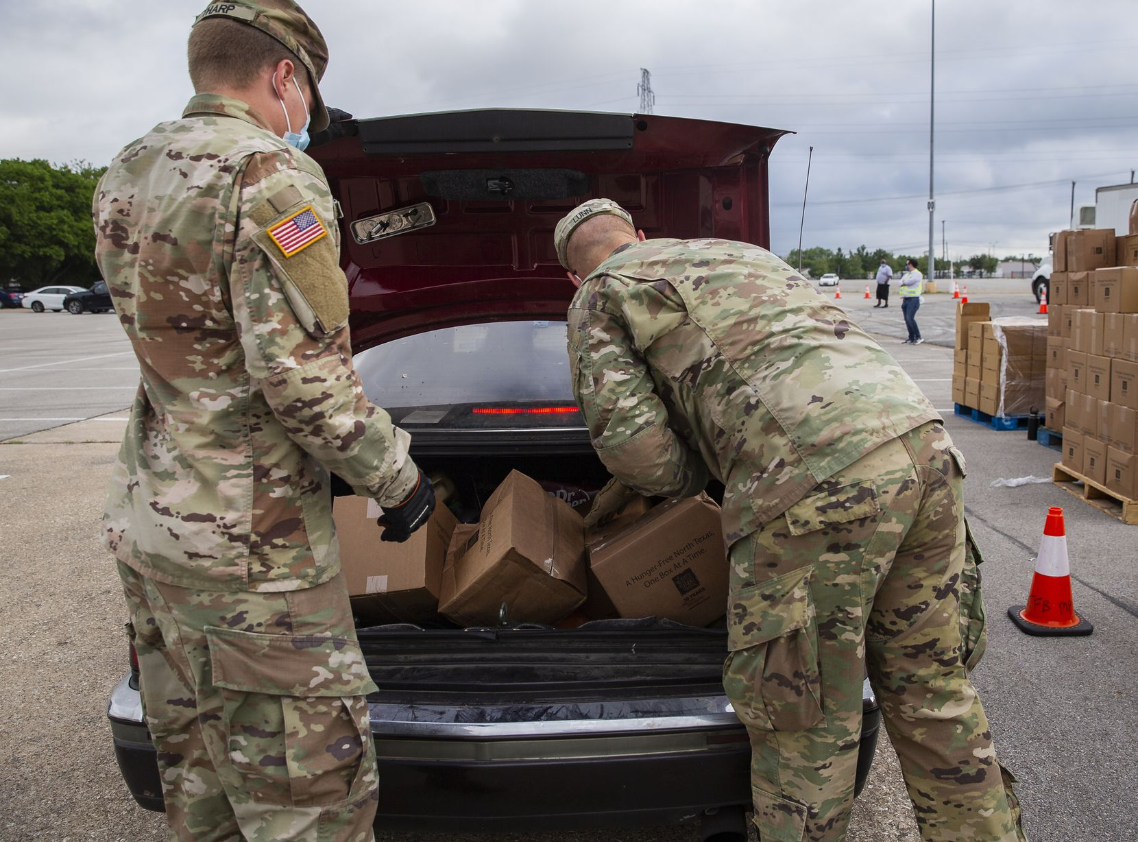 National Guard soldiers load Elise Earnhart Bigony's 1992 Cadillac Eldorado with food from the North Texas Food Bank at Fair Park on May 14, 2020, in Dallas. Bigony was the first in line at 1:45 a.m. with distribution set to begin at 9 a.m.