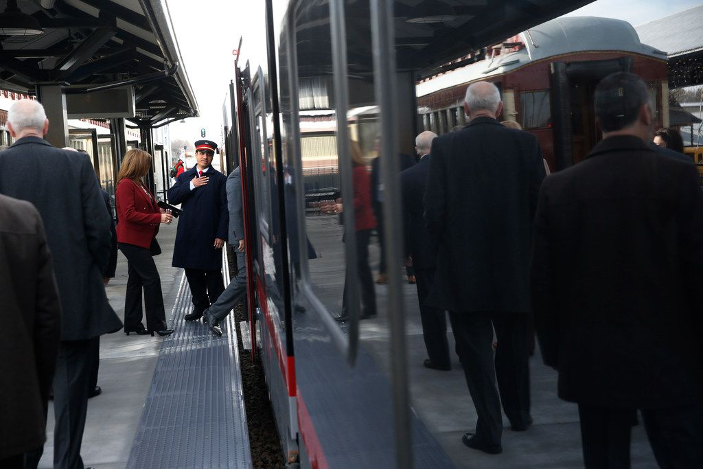 Daniel Jiminez, conductor, greets people Monday as they board the Trinity Metro TEXRail  at the Grapevine/Main Street Station in Grapevine for its maiden trip to DFW International Airport.