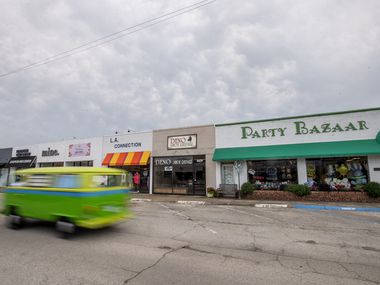 A brightly painted Volkswagen bus drives past shuttered small businesses near Lovers Lane and the Dallas North Tollway. When retail shops open again, a government loan program would make it much easier for them to hold on to their employees.