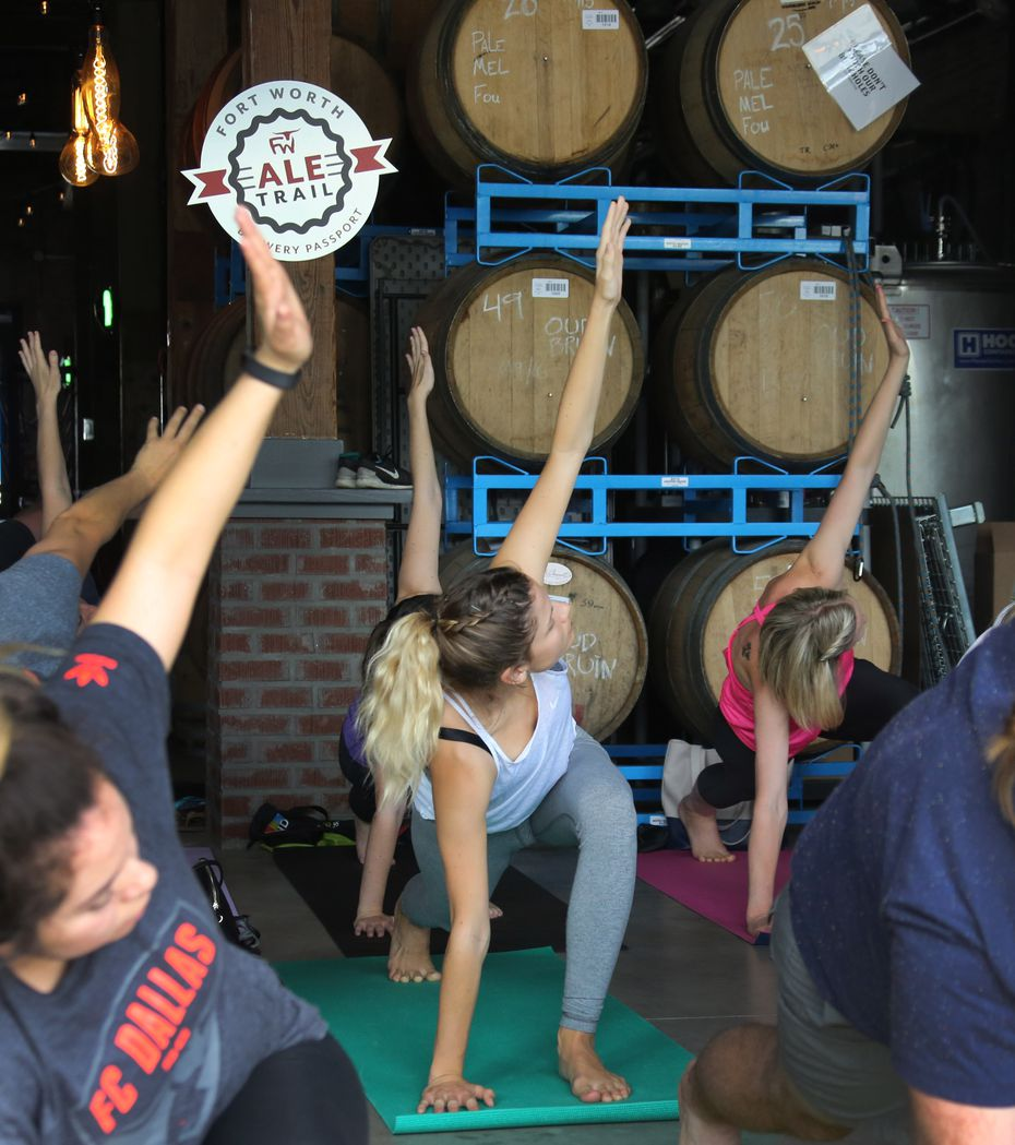 Yoga class takes place in the shadow of beer kegs at Collective Brewing Project in Fort Worth in April 2017.