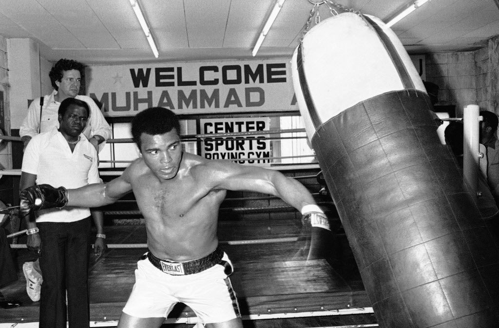 In this Wednesday, June 23, 1976 file photo, Muhammad Ali throws a left punch at a sandbag during workout at a gym in Tokyo. Later in the week, the world heavyweight boxing champion met Japanese pro wrestler Antonio Inoki in the world's Martial Arts Championship.