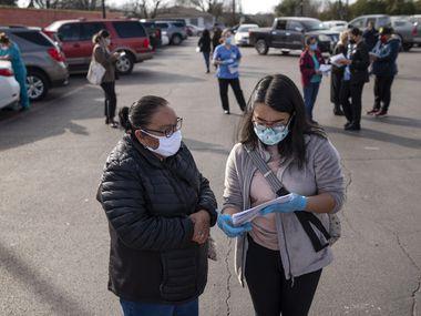 María Hernández, de 68 años, recibe información con ayuda de la enfermera Ruth Olvera (der.) durante un evento para registrar personas para la vacuna contra covid-19 realizado en Super Mercado Monterrey y promovido por los Servicios Humanos y de Salud del Condado de Dallas.
