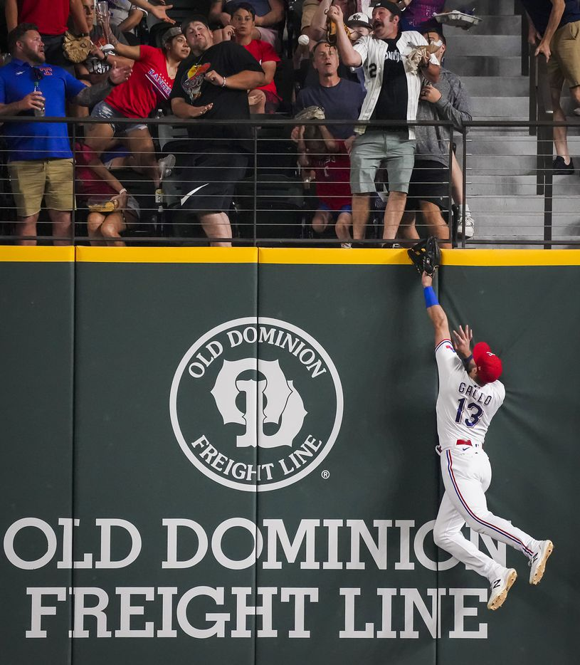 Texas Rangers right fielder Joey Gallo (13) leaps at the wall as 3-run home run off the bat of Detroit Tigers pinch hitter Eric Haase lands in the front row of the crowd to tie the game during the seventh inning at Globe Life Field on Tuesday, July 6, 2021.