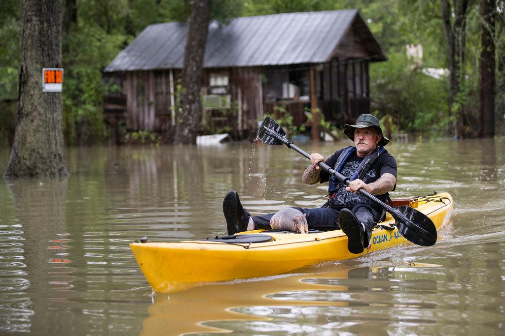 Donnie McCulley paddles out from a flooded neighborhood caused by heavy rain spawned by Tropical Depression Imelda with an armadillo as a passenger on Thursday, Sept. 19, 2019, in Patton Village.
