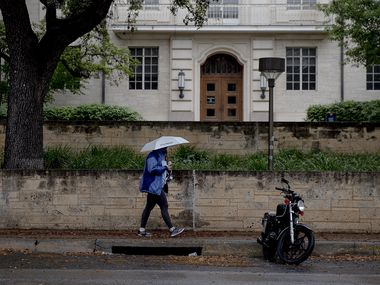A woman passes by a stretch of open motorcycle parking spots on the University of Texas campus on March 30, 2020, in Austin, Texas.