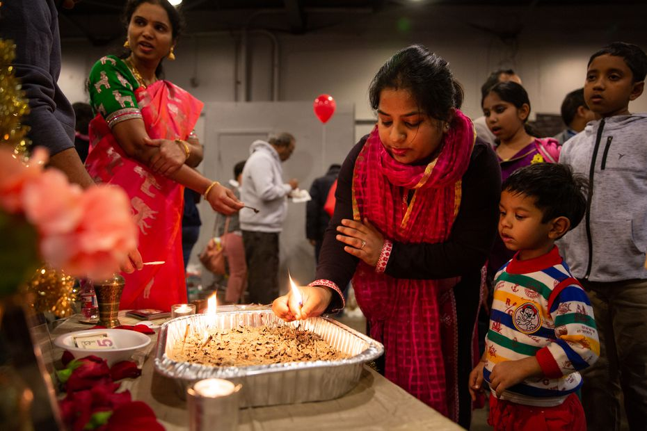 Sonam Modi and her son Kush Gupta place a light at a traditional altar during Diwali Mela on Saturday in Fair Park.