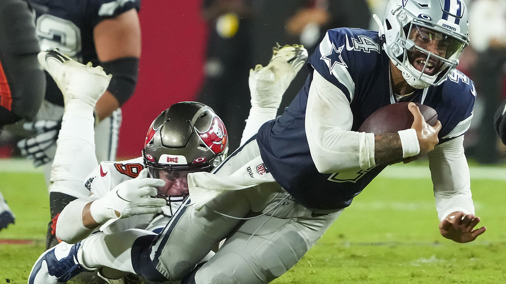 Dallas Cowboys quarterback Dak Prescott (4) is tripped up by Tampa Bay Buccaneers linebacker Joe Tryon-Shoyinka (9) during the first half of an NFL football game at Raymond James Stadium on Thursday, Sept. 9, 2021, in Tampa, Fla.