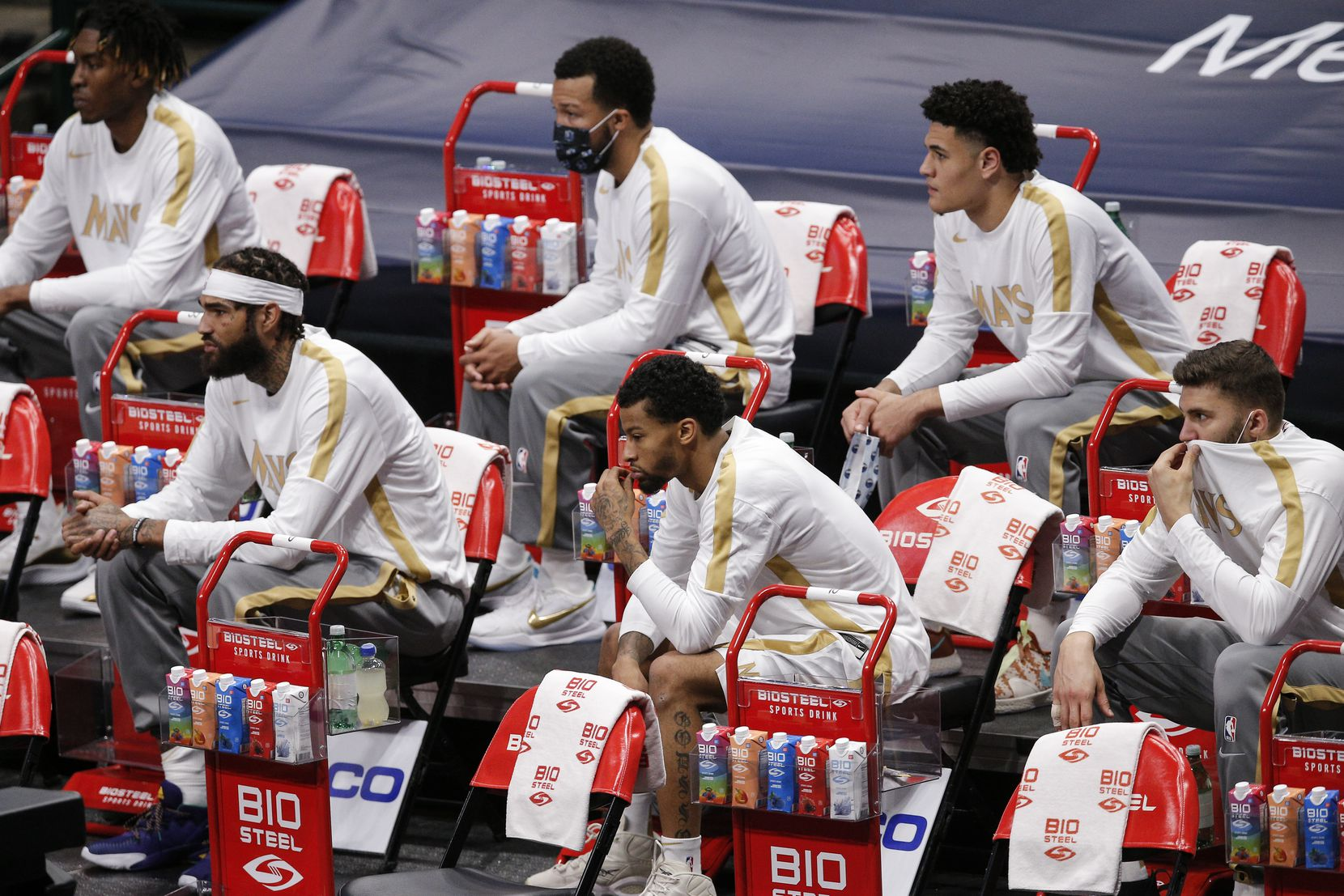The Dallas Mavericks reserve players sit socially distanced on the sidelines during the first half of an NBA basketball game against the Miami Heat, Friday, January 1, 2021. (Brandon Wade/Special Contributor)
