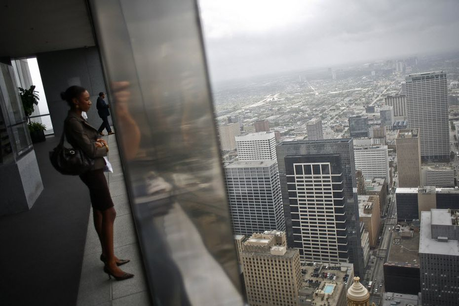 "A woman looks at the Houston skyline from the city's Chase Tower Observation Deck in a photo from 2009. T&L's ranking said plentiful luxury shopping helps ""Houstonians always look their best."""