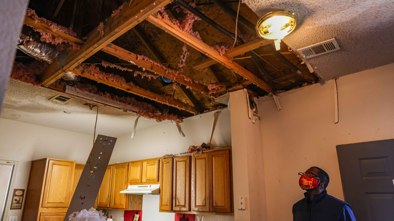 Benny Henderson, 53, takes a look at his mother apartment ceiling at Westmoreland Heights in Dallas on Saturday, where it collapsed over the kitchen due to water damage after the snow storm Uri hit Dallas this week. In Mesquite, low-income homeowners are eligible for financial assistance for home repairs.